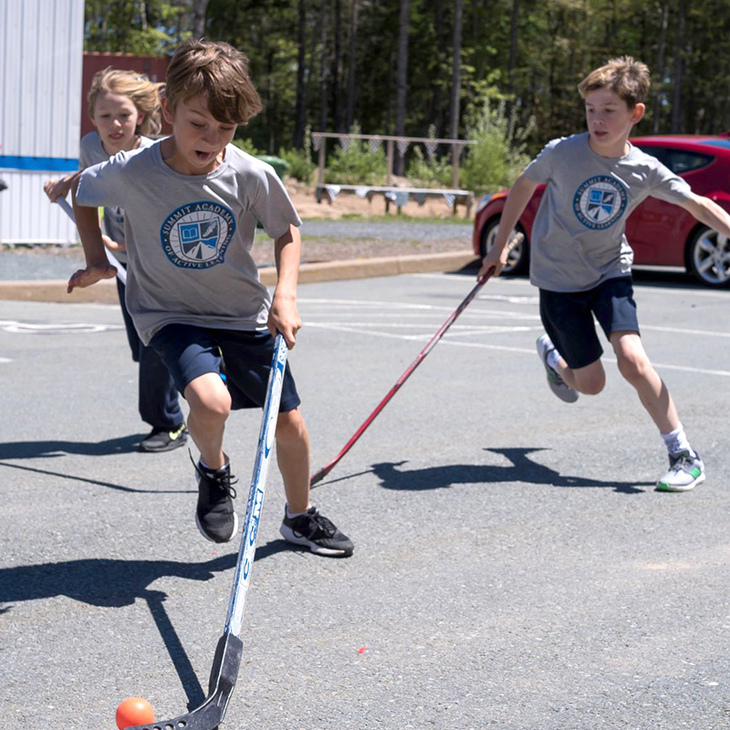 Summit Academy students playing a game of street hockey