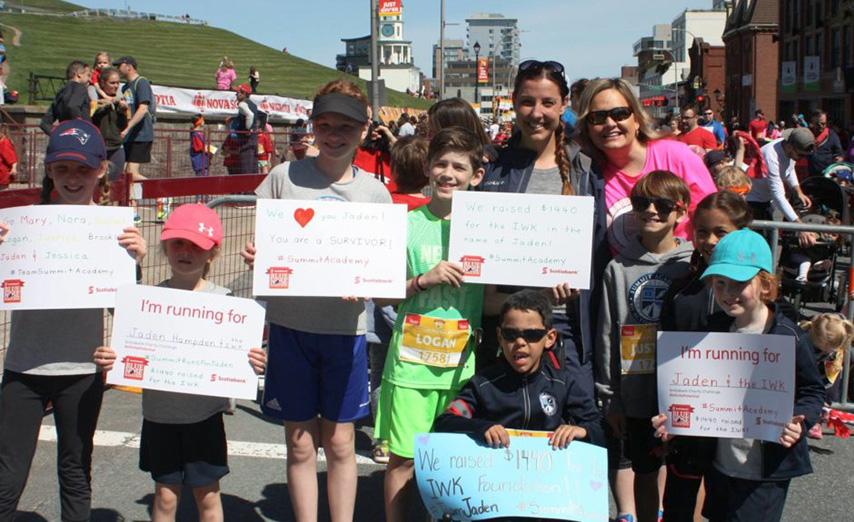 moms & kids at Bluenose marathon holding signs