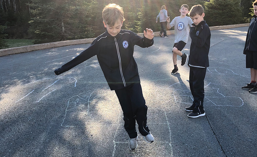 boy playing hop scotch